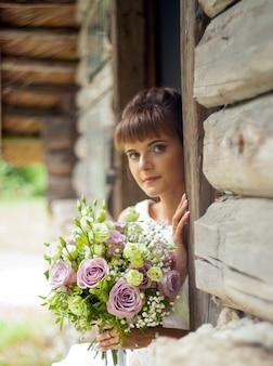 Schönes brautporträt im rustikalen stil. brautfrisur. blumenstrauß mit rosen.
