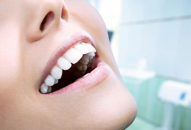 Schönes breites lächeln der jungen frischen frau mit großen gesunden weißen zähnen. über hintergrund isoliert