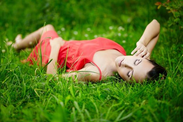 Schönes brünettes frauenmodell, das im grünen sommerhellgras im park mit make-up im roten kleid liegt.