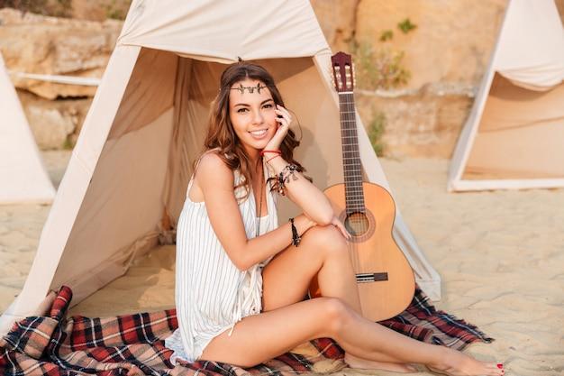 Schönes brünettes hippiemädchen, das am zelt sitzt und kamera betrachtet