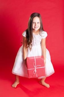 Schönes brünettes kind im weißen kleid nimmt geschenkbox vom boden auf