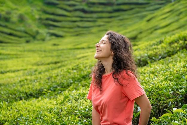 Schönes brünettes mädchen, das in der mitte des teetals zwischen grünen teebüschen aufwirft.