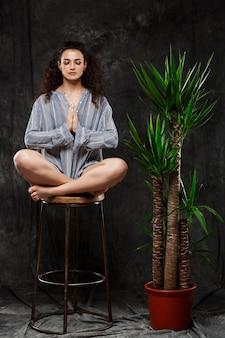 Schönes brünettes mädchen, das in tropischen pflanzen über graue wand meditiert