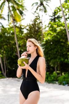 Schönes brünettes mädchen im schwarzen bikini, das kokoswassermilch nahe dem ozean trinkt