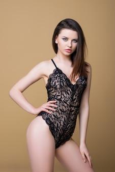 Schönes brünettes mädchen im sexy schwarzen schnürsenkel-kombinationsoverall, der lokalisiert auf beigem hintergrund aufwirft. mode dessous. luxusfrau.
