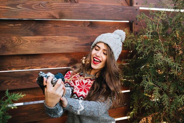 Schönes brünettes mädchen im winterhut, das selbstporträt auf kamera auf hölzernem außen macht.