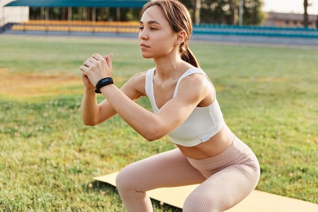 Schönes brünettes mädchen macht kniebeugen im stadion, trainiert beine und gesäß im freien, frau trägt weißes tanktop und beige leggins