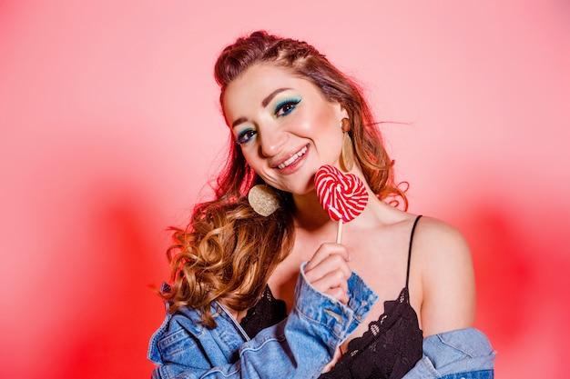 Schönes brünettes mädchen mit blauem make-up, zöpfen und einer ärmellosen jeansweste, die auf einem roten hintergrund mit einem herzförmigen lutscher aufwirft. horizontales foto