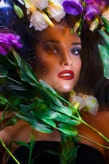 Schönes brünettes mädchen mit hellem schminken, das unter eustomas liegt.