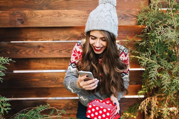 Schönes brünettes mädchen mit langen haaren und roten lippen auf hölzernem freien. sie trägt eine strickmütze, ein telefon und eine geschenkbox. sie sieht glücklich aus.