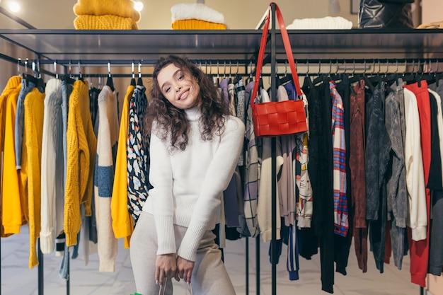 Schönes brünettes mädchen mit lockigem haar wählt kleidung in einer boutique in einem modernen bekleidungsgeschäft für einen zeitraum von rabatten