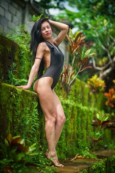 Schönes brünettes mädchen mit perfektem körper im badeanzug im grünen park auf dem bali