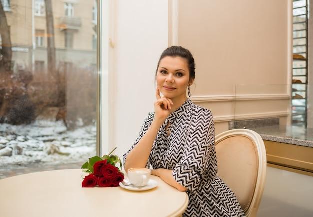 Schönes brünettes mädchen sitzt mit einer tasse kaffee und rosen am tisch in einem café