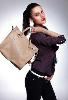 Schönes brünettes modell, das handtasche hält