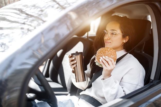 Schönes brünettes modell hat mittagessen in einem auto.