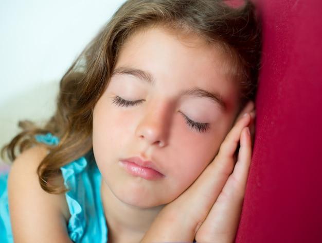 Schönes brunete kindermädchen, das hände zusammen schläft