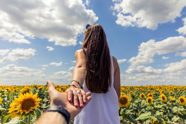 Schönes brunett mädchen im weißen kleid, das hand in hand zum sonnenblumenfeld geht.