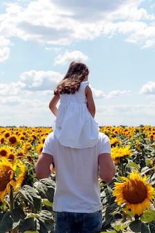 Schönes brunett mädchen im weißen kleid im stutzen ihres vaters, der zum sonnenblumenfeld geht
