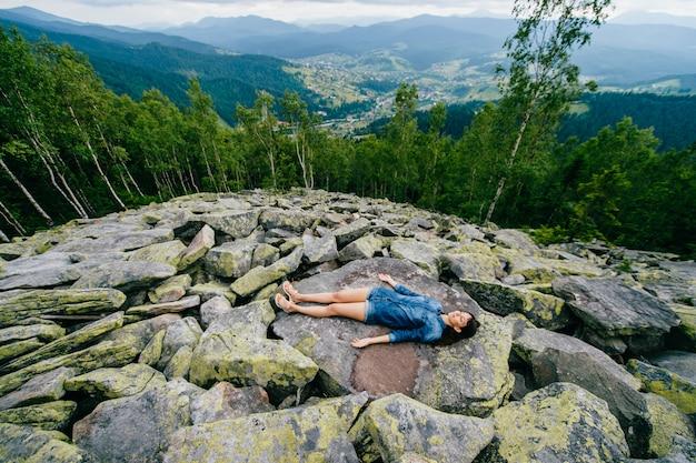 Schönes brunettemädchen, das auf steinen in den bergen liegt.