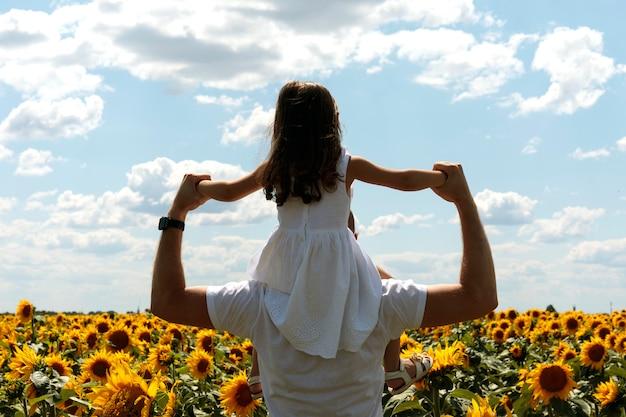 Schönes brunettemädchen im weißen kleid im hals ihres vaters, der zum sonnenblumenfeld geht