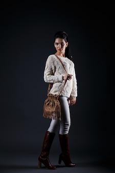 Schönes brunettemädchen in der beige strickjacke und in der braunen tasche