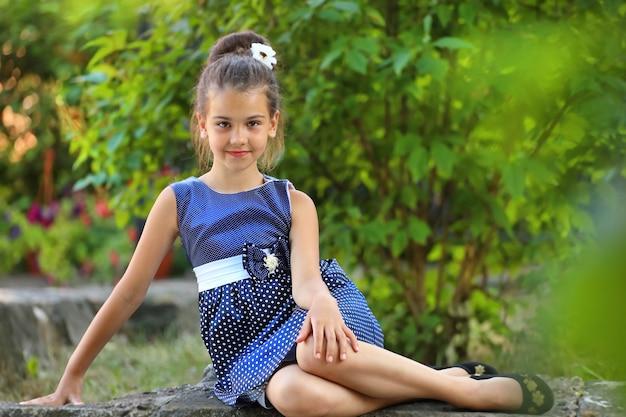 Schönes brunettemädchen in einem blauen tupfenkleid im sommer im park. stilvolles kind in der natur. foto in hoher qualität