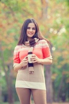 Schönes brunettemädchen mit cup im park.