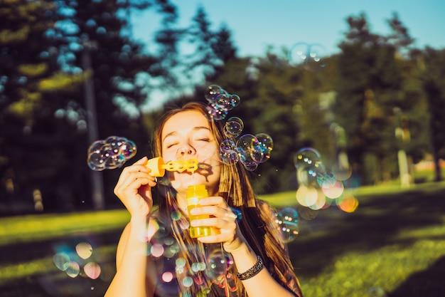 Schönes brunettemädchen mit langen haaren bläht seifenblasen im park auf