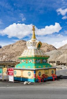 Schönes buddhistisches stupa mit dem blauen himmel bewölkt nahe pangong see in leh, ladakh,