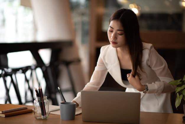 Schönes charmantes lächeln der jungen asiatischen geschäftsfrau, das laptop und computer im büro verwendet