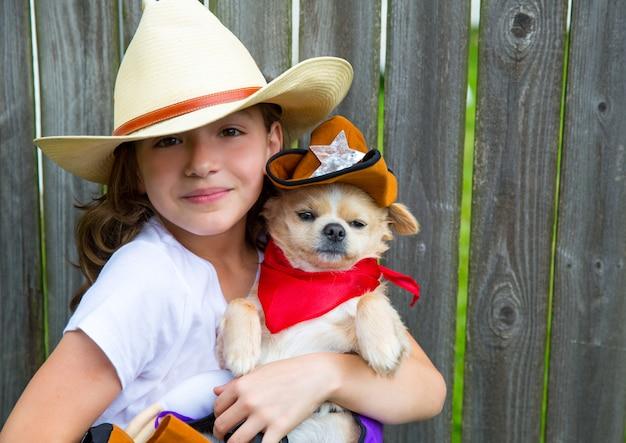 Schönes cowboykindermädchen, das chihuahua mit sheriffhut hält
