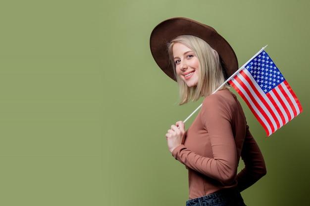 Schönes cowgirl in einem hut mit flagge der vereinigten staaten von amerika