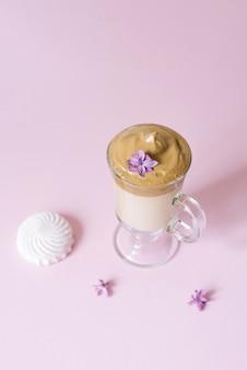 Schönes dalgon-kaffeegetränk. kaffeetasse in klarem glas mit schaum und lila blume auf einem flieder