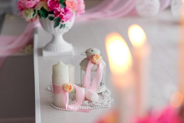 Schönes dekor von kerzen und blumen. weiß-rosa-töne.