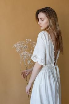 Schönes dünnes junges mädchen mit dem langen haar im weißen kleid mit der blanken rückseite, die auf beige hintergrund aufwirft und weiße blumen in ihren händen hält