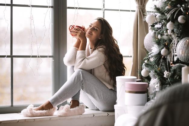 Schönes dunkelhaariges mädchen in hosen, pullover und warmen hausschuhen hält eine rote tasse, die auf der fensterbank eines panoramafensters im raum neben dem neujahrsbaum und geschenken sitzt.
