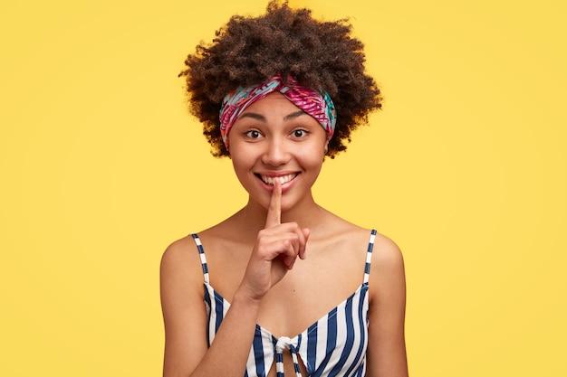 Schönes dunkelhäutiges fröhliches modell trägt lässiges gestreiftes oberteil, buntes stirnband auf der stirn
