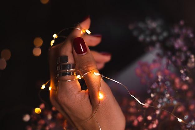 Schönes dunkles foto der handfinger der frau mit großem silbernem ring auf blumen und leuchtenden lichtern