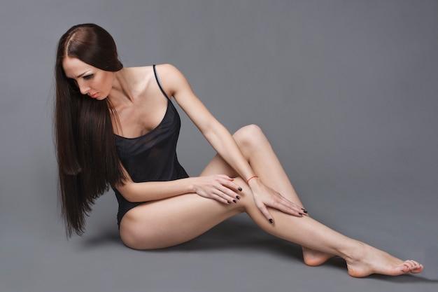 Schönes dunkles haarmädchen mit langen schlanken beinen, die auf dem grauen hintergrund sitzen
