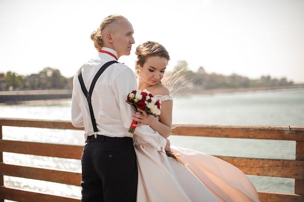 Schönes ehepaar steht auf dem holzsteg am see. vorstellung der hochzeit