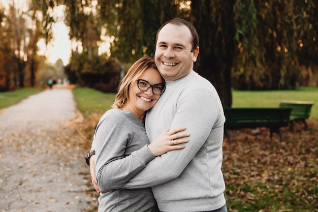 Schönes ehepaar umarmt und lacht beim betrachten der kamera im park.