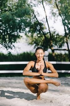 Schönes eignungsmädchen, das auf einem strand am sonnigen sommertag im sexuellen bikini trainiert