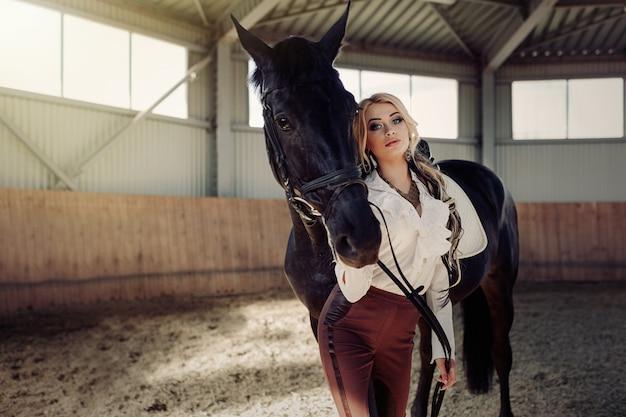 Schönes elegantes junges blondes mädchen, das nahe ihrem pferd kleidet uniformwettbewerb steht