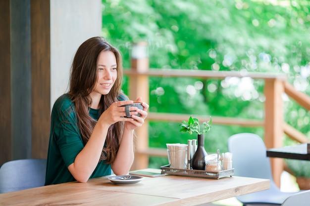 Schönes elegantes mädchen, das café am im freien frühstückt. trinkender kaffee der glücklichen jungen städtischen frau