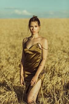 Schönes elegantes modell bei sonnenuntergang in einem maisfeld mit elegantem kleid