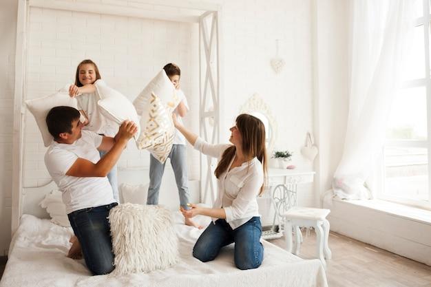 Schönes elternteil mit ihrem kind, das kissenschlacht auf bett im schlafzimmer spielt