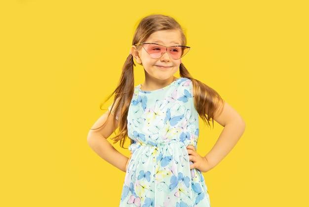 Schönes emotionales kleines mädchen isoliert. porträt des glücklichen kindes, das ein kleid und eine rote sonnenbrille steht und trägt. konzept des sommers, der menschlichen gefühle, der kindheit.