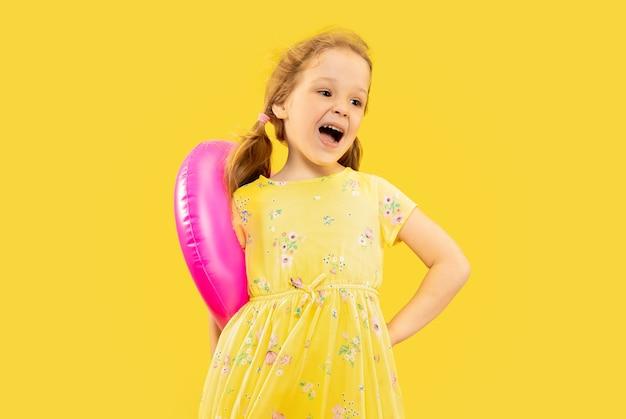 Schönes emotionales kleines mädchen lokalisiert auf gelb