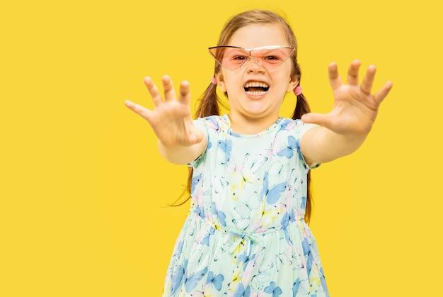 Schönes emotionales kleines mädchen lokalisiert auf gelbem hintergrund. halblanges porträt eines glücklichen kindes, das steht und ein kleid und eine rote sonnenbrille trägt. konzept des sommers, der menschlichen gefühle, der kindheit.