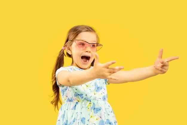 Schönes emotionales kleines mädchen lokalisiert auf gelbem raum. halblanges porträt eines glücklichen kindes, das steht und ein kleid und eine rote sonnenbrille trägt
